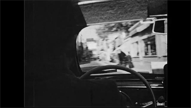 1950s: View from behind man driving car. Tracking shot from car, driving down street.