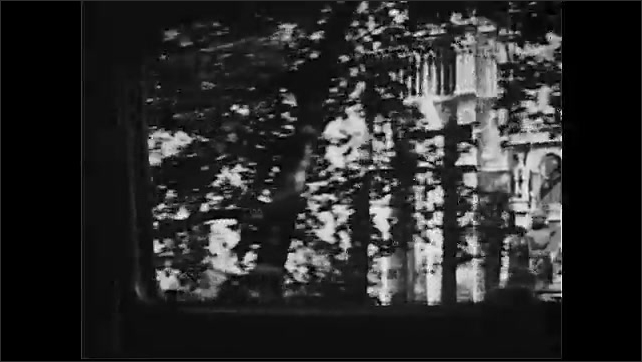 1950s: Tracking shot from car, passing cathedral. Tracking shot past building.