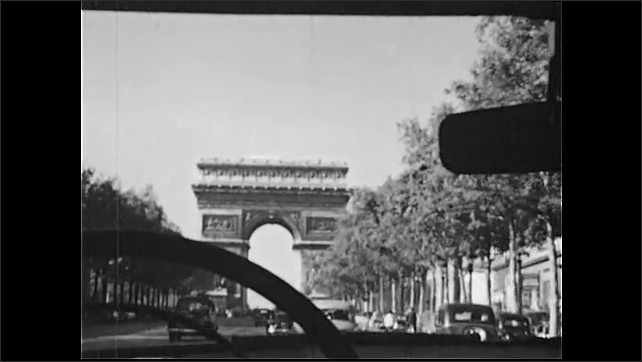 1950s: Tracking shot from car, driving on city street. Driving toward arch. High angle view, boy looks at map.