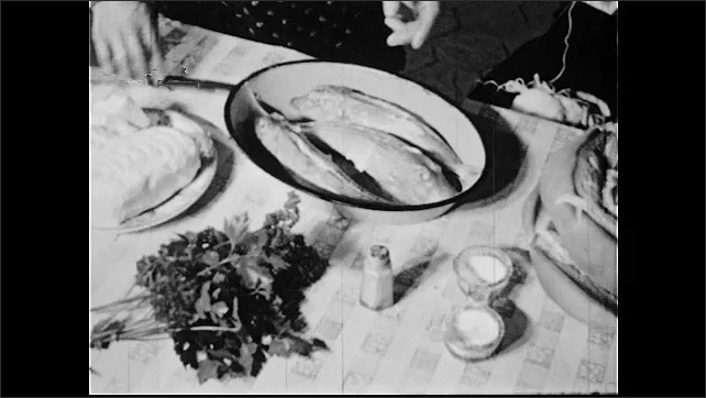 1950s: Hand takes food from shelf. Woman carries plate to table, puts butter on fish. Hands prepare fish. Pan across ocean, piers.