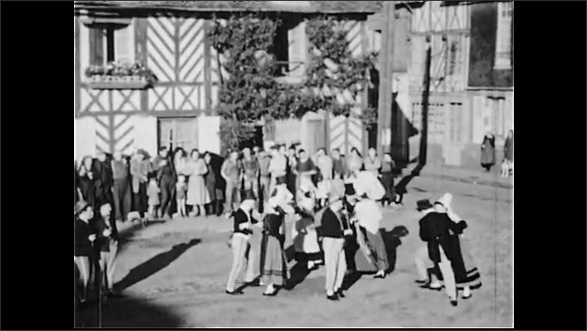 1950s: Close up of man talking. Man talking to boy. View of cathedral spire. High angle view, people dance in square.