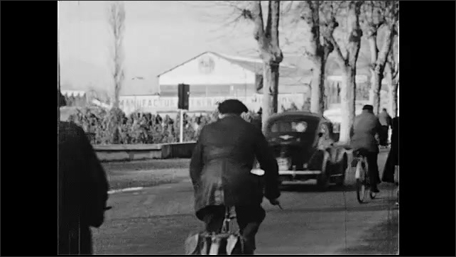 1950s: People dancing in square. Long shot of factory. Truck driving through factory. People ride bikes down street. Men walk past factory. People picking vegetables in field.