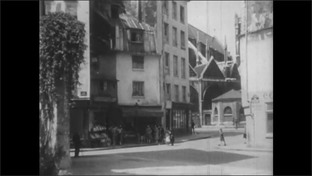 1950s: People walk on narrow street. Front door of a church. People walk on the street with medieval buildings around. Two police officers stand in front of police station.