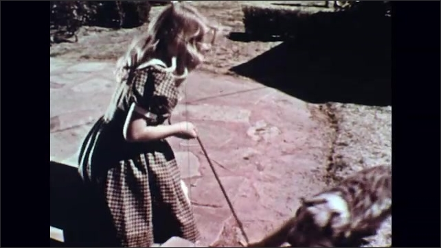 UNITED STATES 1950s : Girl Plays Tug with Dog in Yard