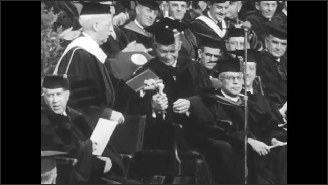 1950s: High angle view, audience applauding. Dwight D Eisenhower sits on chair on stage. Audience applauding.