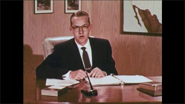 1950s: UNITED STATES: man at desk in suit speaks to camera. Man wears glasses. Map of American roads on wall.