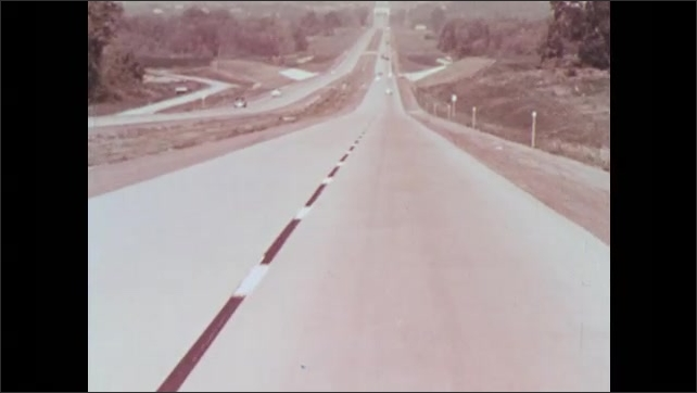 1950s: UNITED STATES: rear view of car on freeway. Man drives car on freeway. Blurred view of freeway lane.