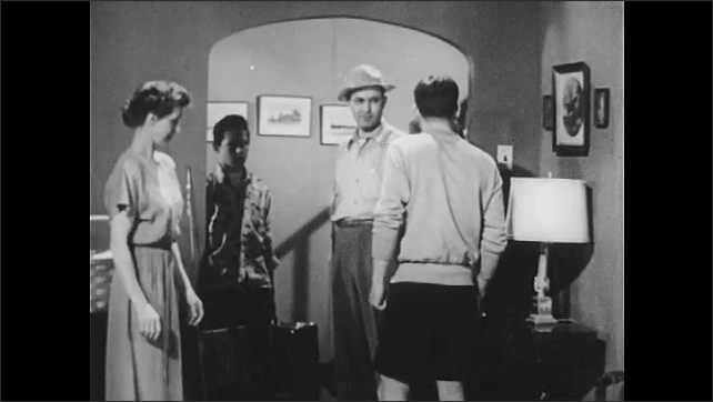 1950s: Family stands in living room, mother pleads with son, places both hands on his shoulders. Sister talks, taunts brother, brother walks over, intimidates her. Brother talks.