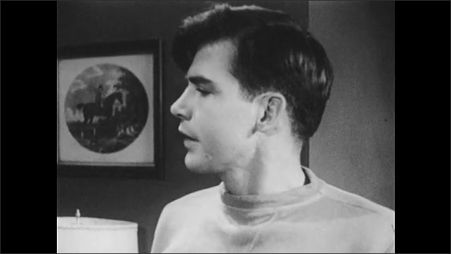 1950s: Family stands in living room, teenage son talks, looks frustrated, depressed. Father talks, younger brother pouts, talks, looks down, disappointed.