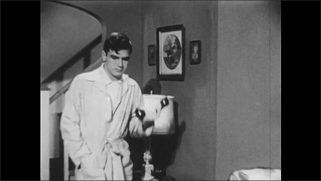 1950s: Living room, teenage boy in robe picks up phone, nods, looks at receiver, shrugs, looks disappointed, gets idea, picks up phone, looks frustrated.