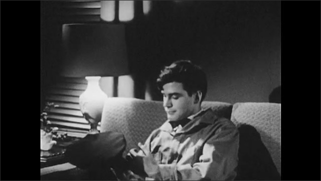 1950s: Living room, teenage boy sits on couch in the dark beside table lamp, looks pensive, looks around room, nods, thinks to himself, looks down. Boy sits up straight, smiles.