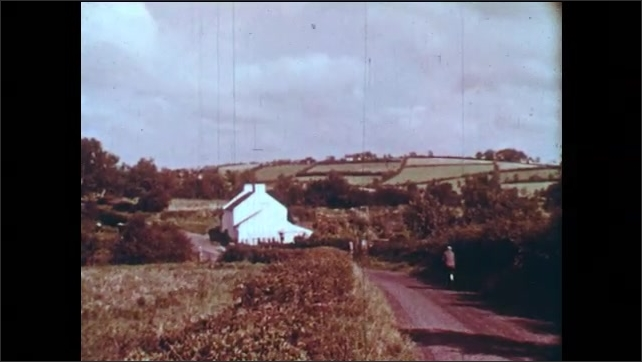 1960s: Man walks through countryside. Man rides bicycle down country road. Man walks with dog through countryside. Man holds apron bunched up at waist.