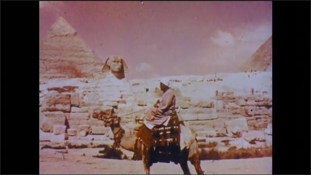 1960s: Man folds stack of linen fabric. Man rides camel in front of pyramids, Sphinx. Patterned fabric pillow.