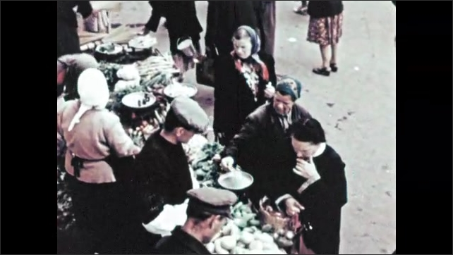 1960s RUSSIA: Men and women choose tomatoes at open air market. Men and women shop for vegetables at street market in Moscow.