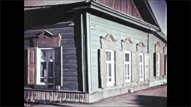1960s RUSSIA: Girl runs and skips past large wooden house with many windows and shutters.