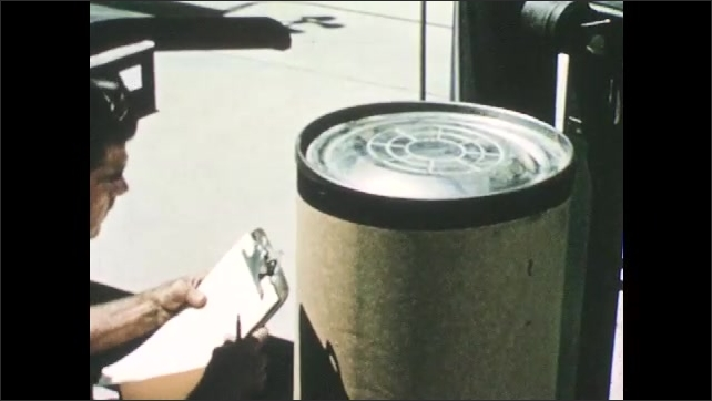 1950s: Farm.  Man takes hose out of barrel and puts on lid.  Man holds clipboard and writes on barrel.