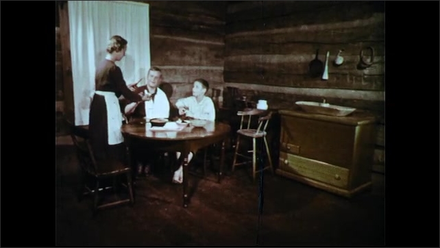 1950s: Man talks to woman and boy. Woman serves man and boy at table. Woman serves bread, sits down. Food on table, knife scoops butter. Boy puts on shirt, exits room.