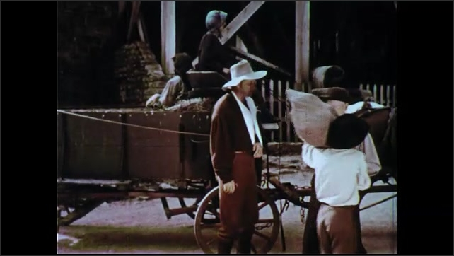 1950s: Men shake hands next to wagon. Man talking. Woman and girl in wagon. Boy carries sack, walks away with man. Boy watches man pour grain into machine. Man and boy talk.