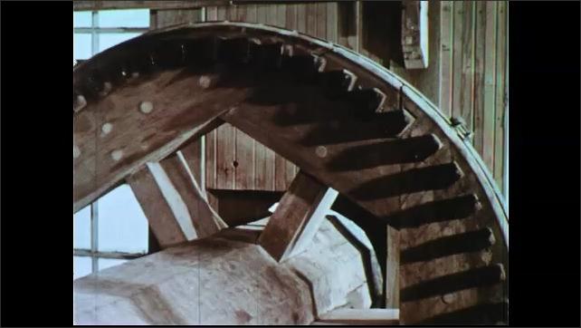 1950s: Waterwheel turning. Water pouring over wheel. Gears moving in mill. Boy feels grain in hopper, tilt down to grinder.