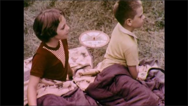 1970s: Forest ranger fries eggs and stirs cocoa over a campfire. Girl and boy campers ask if breakfast is ready. Forest Ranger shakes head no. Girl and boy pick up a wheel labelled Multiple Use.