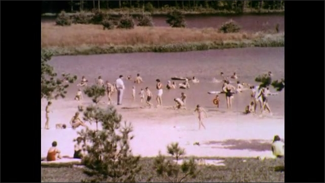 1970s: Car parks at beach parking lot. Families play in lake and on the beach.