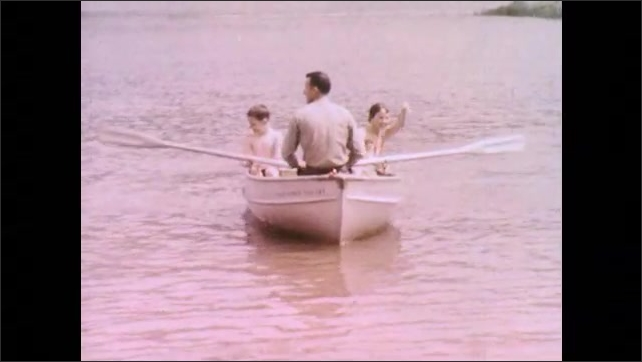 1970s: Sailboat sails across lake with three passengers. Forest Ranger rows boat to shore. Cookout outside of cabin.