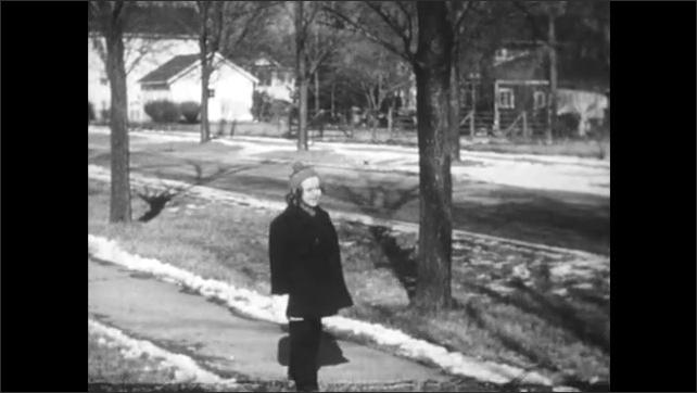 1950s: Boy inside house looks out window, shrugs. Child in winter coat outside kicks snow along sidewalk. Man walks down sidewalk carrying paper bag.