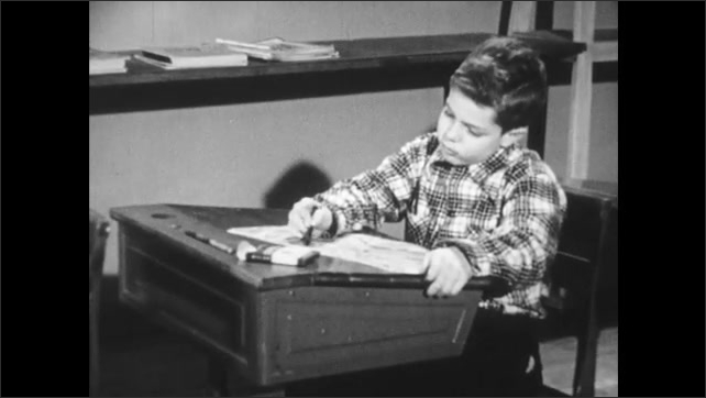 1950s: Classroom, boy sits at desk, closes book, looks at boy in front of him drawing. Boy looks down at book, looks confused.