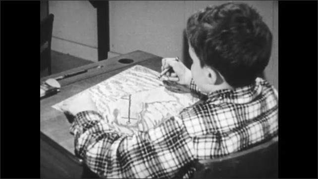 1950s: Classroom, boy sits at desk drawing with crayons, scribbles repeatedly.