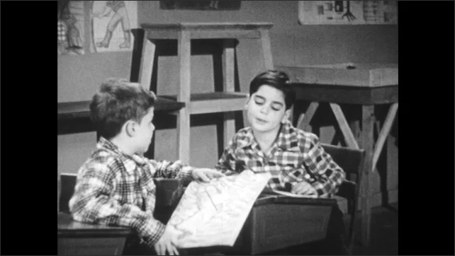 1950s: Classroom, boy at desk draws on paper. Boy behind him taps on his shoulder, he shows his drawing. Boy and girl in winter coats stand in driveway in snowy neighborhood and talk.