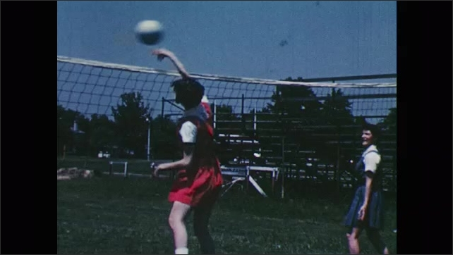 1950s: Girls practice serving volleyball.