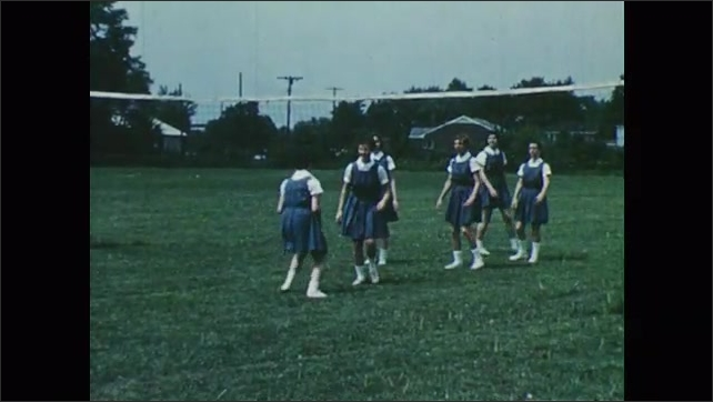 1950s: Girls practice playing volleyball, hit volleyball off net.