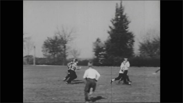 A boy holds a football while another one kicks it to start the game