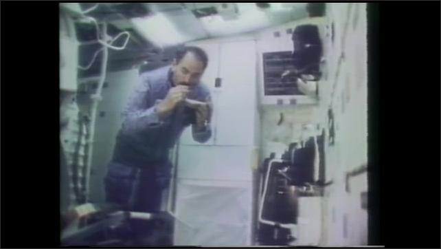 1990s: Spacecraft landing on runway. Man drinking from pouch in spacecraft. Man swallows liquid in zero gravity.