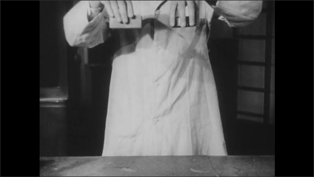 1950s: Man stands in laboratory. Man picks up and drops objects onto counter.