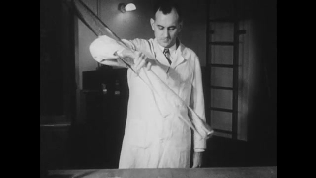 1950s: Man holds glass tube, flips tube upside down. Feather and coin fall together inside the tube.