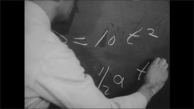 1950s: Man writes formulas on blackboard. Ball rolls down ramp.