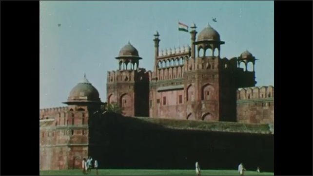 1960s: Indian flag waves on top of ancient building. People walk on grass in front of building.