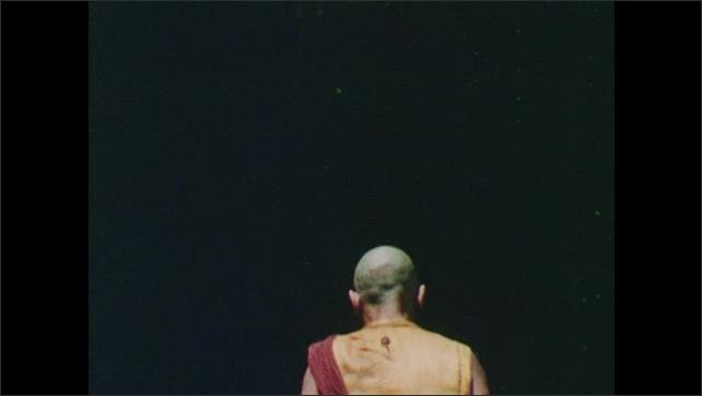 1960s: Monk walks into temple. Statue of buddha.