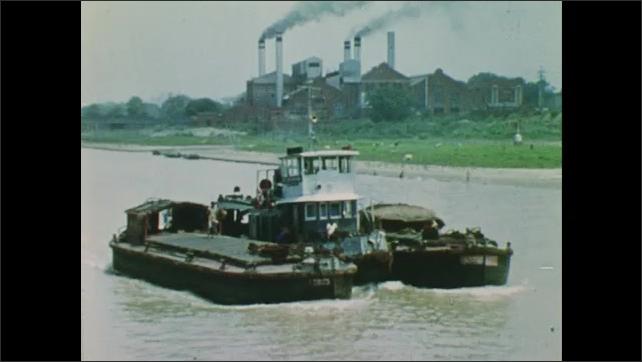 1960s: Boats travel along Ganges. Large bridge.