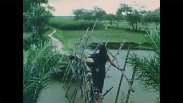 1960s: Woman carries jug, walks down steps, looks up, walks across makeshift bridge.
