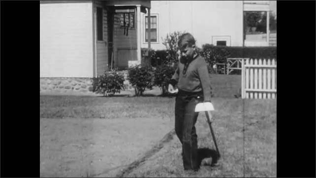 1940s: UNITED STATES: boy makes shallow furrow in soil. Boy walks across garden. Boy empties seeds into hand