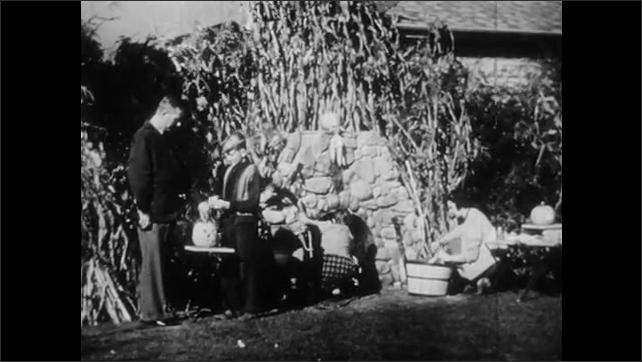 1940s: UNITED STATES: girl picks sweet corn in garden. Family prepare food on fire. Harvest time in garden