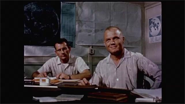 1960s: John Glenn and  Deke Slayton seated at table, Slayton talks. Wally Shirra and Gordon Cooper at table, pan to Cooper and Gus Grissom, Cooper talks.