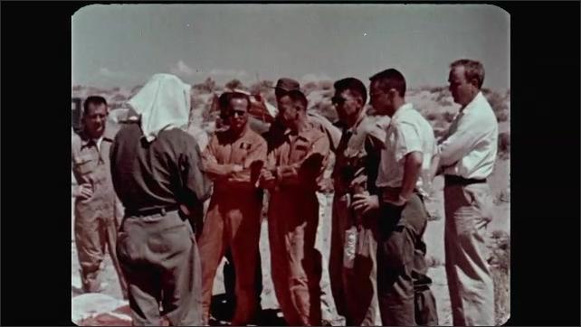 1960s: Long shot, men walking by tents in desert. Men standing in line, man folding towel in foreground. Man puts towel on head.