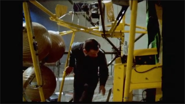 1960s: Deke Slayton and man walk under equipment.