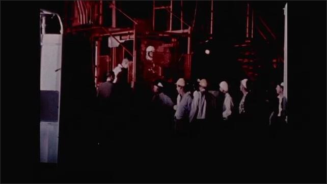 1960s: Alan Shepard at Mercury launch site, walks past men to tower elevator.