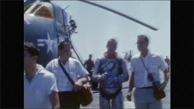 1960s: Helicopters flying with space capsule. View of capsule. Alan Shepard with men. Shepard walking with men. Shepard takes helmet from capsule.