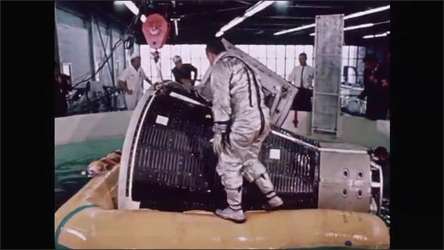 1960s: UNITED STATES: astronaut climbs out of capsule in swimming pool. Life raft around capsule.
