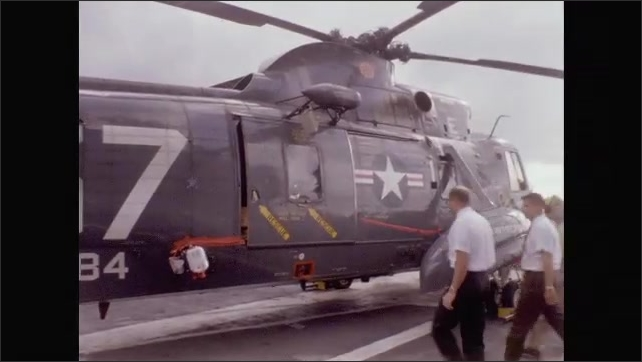 1960s: Helicopter lands on aircraft carrier.  Men open door.  Astronauts walk and greet crowd.